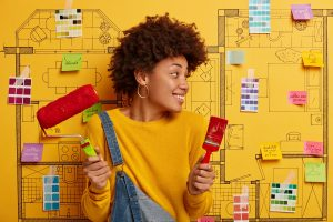 African American female decorator holds paint brush and roller