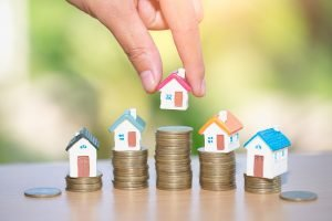 Mini house on stack of coins, Real estate investment