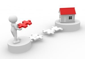 Bridge loan concept: Little white model of person holding red puzzle piece to bridge a puzzle between him and house